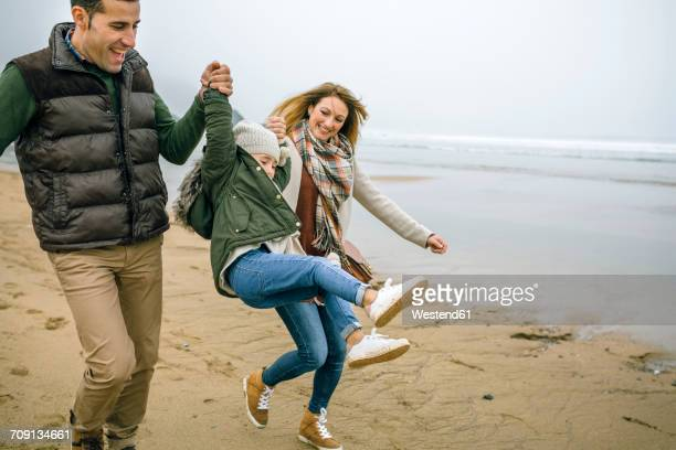 Happy parents lifting up daughter on the beach in winter