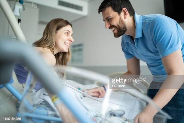 parents heureux regardant et souriant l'un à l'autre à l'hôpital - accouchement photos et images de collection