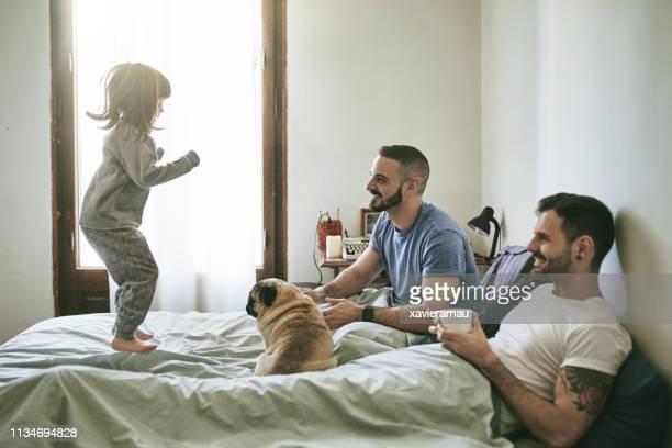 ベッドの上にジャンプ娘を見て幸せな両親 - ゲイ ストックフォトと画像