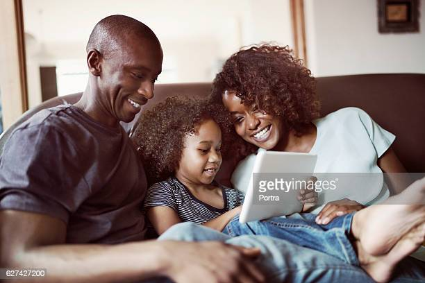 happy parents looking at son using digital tablet - african american family home stock photos and pictures