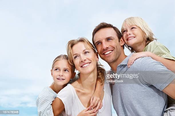 Happy parents piggybacking their children