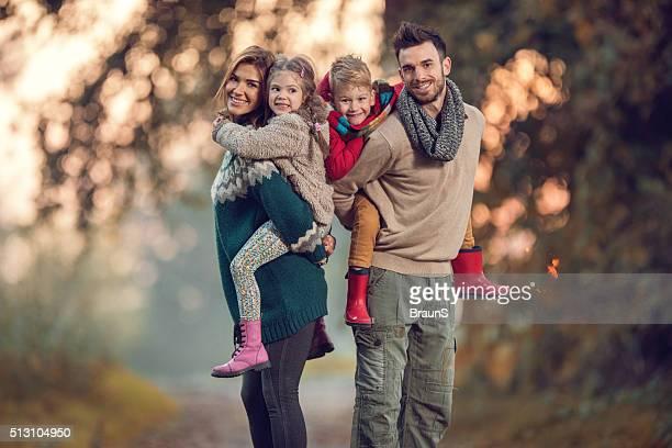 Glückliche Eltern kombinierten Verkehrs bereitgestellt werden Ihre kleinen Kinder im Park.