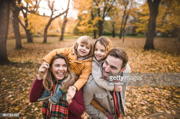 happy parents piggybacking their small kids in autumn day. - famiglia con due figli foto e immagini stock