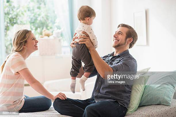Happy parents playing with little son (2-3 years) on bed
