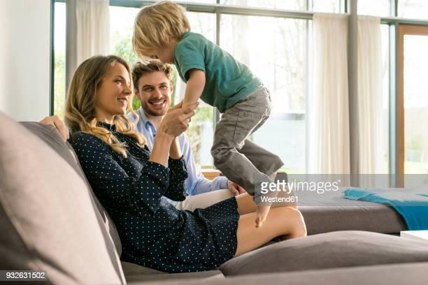 happy parents playing with son on sofa at home - familie mit einem kind stock-fotos und bilder