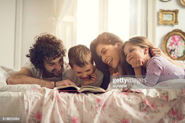 Happy parents reading a book with their children in bed.
