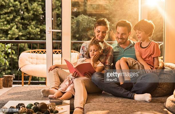 pais feliz lendo um livro com os pequenos crianças. - grupo pequeno de pessoas - fotografias e filmes do acervo