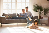 Happy parents relaxing on couch while kid drawing on floor