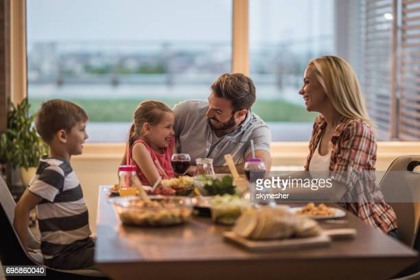 happy parents talking to their children at dinning table. - penthouse girls stock pictures, royalty-free photos & images