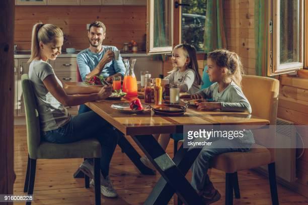 heureux parents de parler à leurs petites filles tout en ayant un repas à la maison. - chalet de montagne photos et images de collection