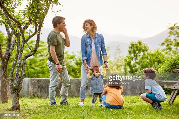 happy parents talking while kids playing on field - baby human age stock pictures, royalty-free photos & images
