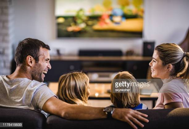 happy parents talking while watching tv with their kids at home. - family watching tv stock pictures, royalty-free photos & images