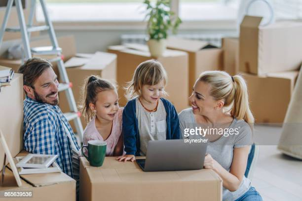 Glückliche Eltern mit Laptop mit ihren Kindern beim Umzug in neues Zuhause.