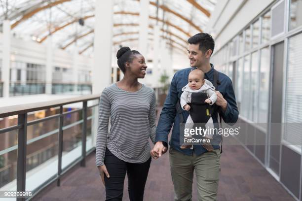 Happy parents walking with their baby in a shopping mall