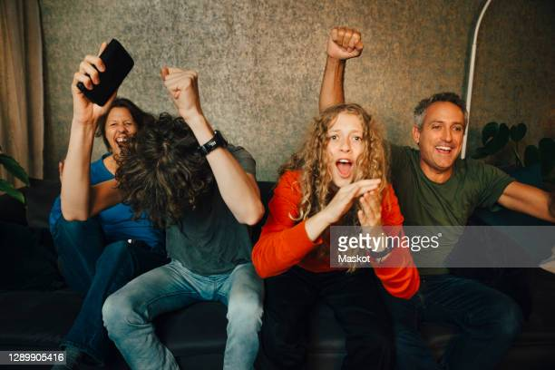 happy parents with children cheering while watching sports in living room at night - spectator stock pictures, royalty-free photos & images