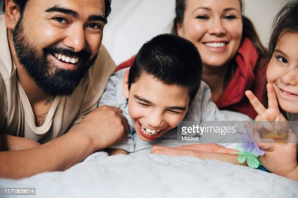 happy parents with children lying on bed at home - autismo foto e immagini stock