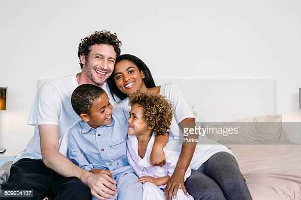 happy parents with children on bed - mixed race person stock pictures, royalty-free photos & images