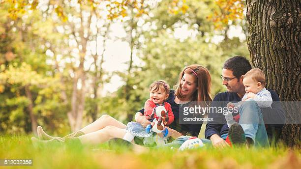 happy parents with children outdoors having a good family time - cute twins stock photos and pictures