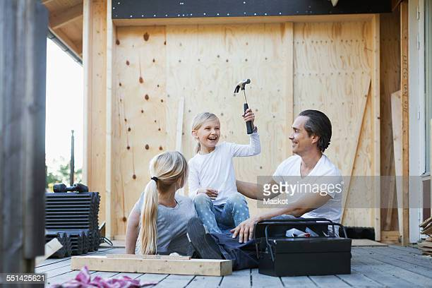 Happy parents with daughter holding hammer while sitting outside house