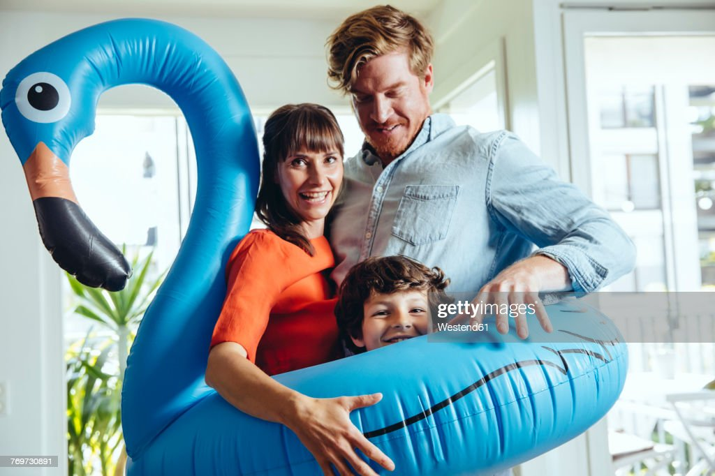 Happy parents with son holding an inflatable flamingo at home : Stock Photo