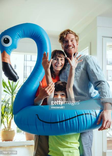 Happy parents with son holding an inflatable flamingo at home