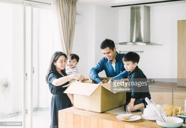 padres felices con hijos desempacando caja de cartón - movilidad fotografías e imágenes de stock