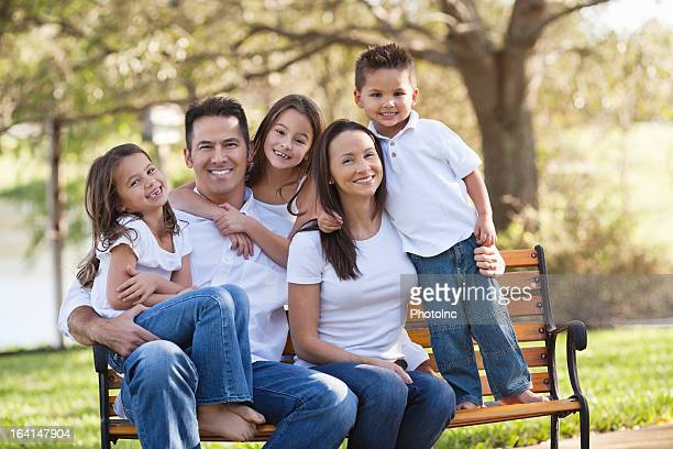 Happy Parents With Three Children At Park