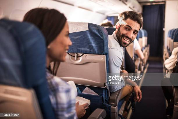 Happy passengers traveling by airplane and talking to each other.