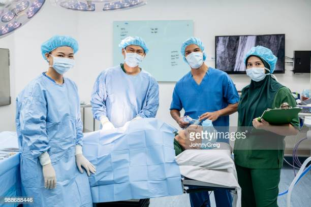 happy patient concept - medical team and senior man in operating theatre - funny surgical mask stock pictures, royalty-free photos & images