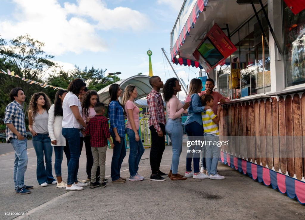 Happy people buying food at an amusement park : Stock Photo