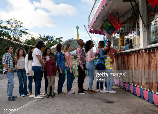 happy people buying food at an amusement park - kiosk stock pictures, royalty-free photos & images