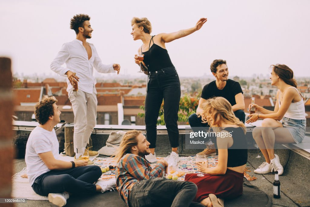 Happy people dancing while enjoying music with friends on terrace at rooftop party : Stock Photo