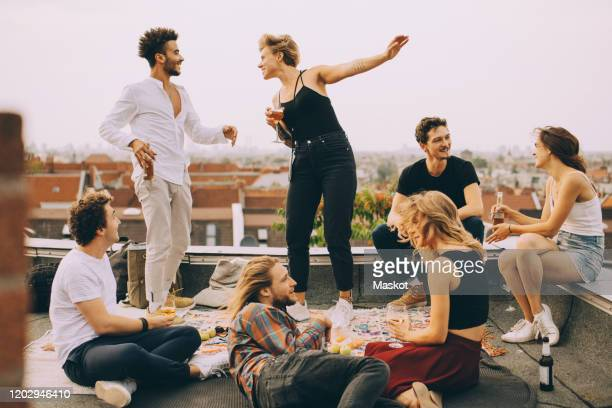 happy people dancing while enjoying music with friends on terrace at rooftop party - 数人 ストックフォトと画像