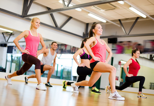 happy people doing lunge exercise in gym 462030223