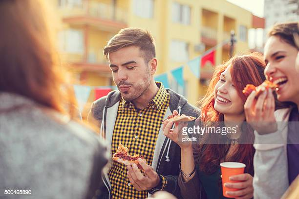 Happy people eating pizza at party