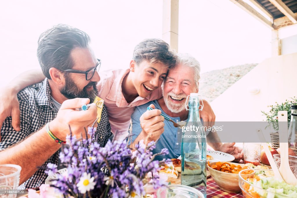 Happy people family concept laugh and have fun together with three different generations ages : grandfather father and young teenager son all together eating at lunch : Stock Photo