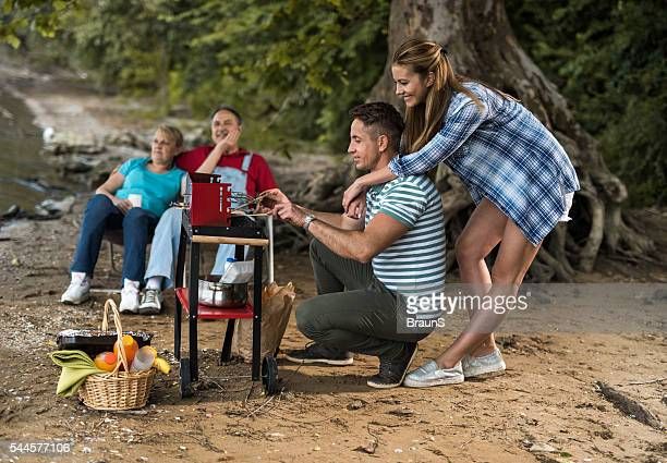 Happy people having a barbecue during the day in nature.