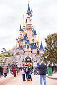 Happy people near castle in the Disneyland Paris.