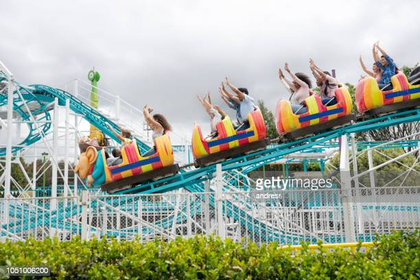 happy people riding on a rollercoaster at an amusement park - amusement park stock pictures, royalty-free photos & images