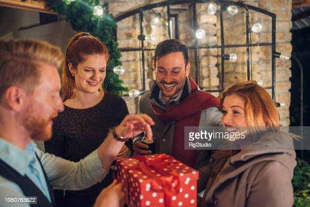 happy people unwrapping a gift - hello december stock pictures, royalty-free photos & images
