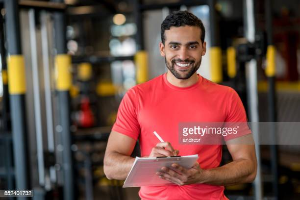Happy personal trainer working at the gym
