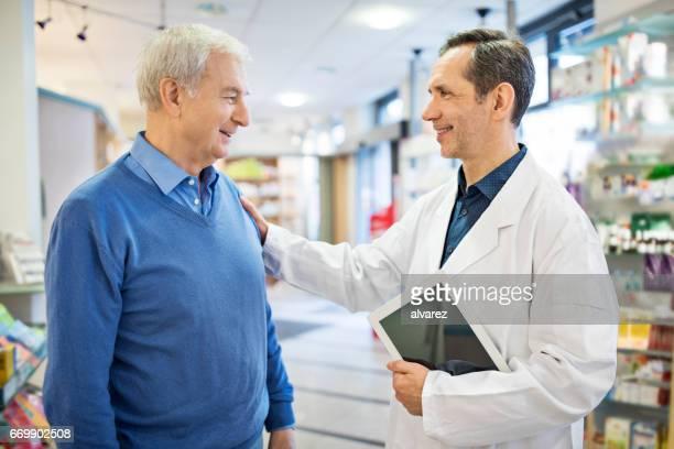 Feliz farmacéutico consolando a hombre mayor en la tienda