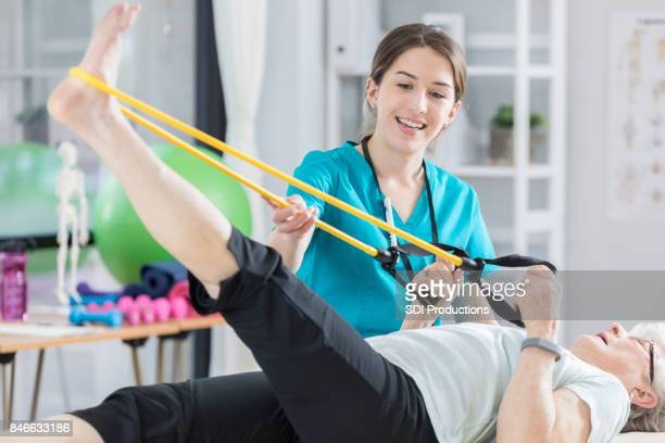 Happy physical therapist uses resistance bands with senior patient