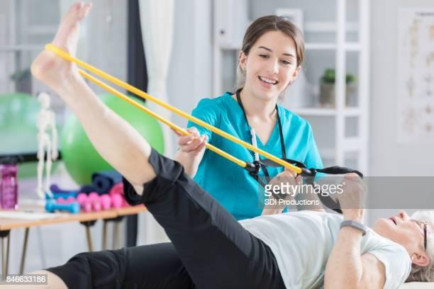 Gelukkig fysiotherapeut gebruikt weerstand banden met senior patiënt