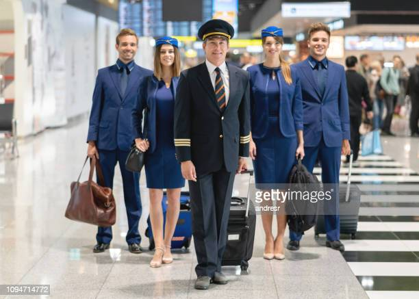 happy pilot with his cabin crew at the airport - crew stock pictures, royalty-free photos & images