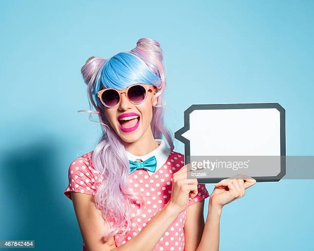 happy pink hair manga style girl holding speech bubble - anime stock photos and pictures