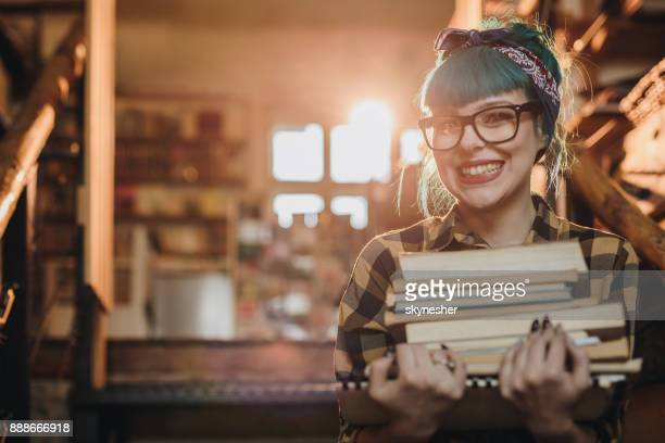 happy pin-up girl with stack of books in library. - stack of books stock photos and pictures