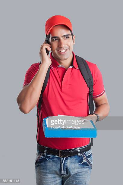 Happy pizza delivery man answering mobile phone against gray background