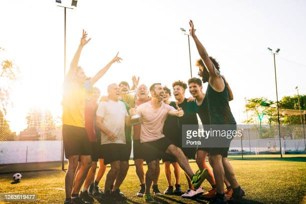happy players cheering with trophy in soccer ground - football team stock pictures, royalty-free photos & images
