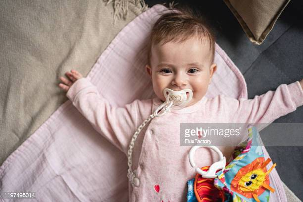 happy playful baby girl - pacifier stock pictures, royalty-free photos & images